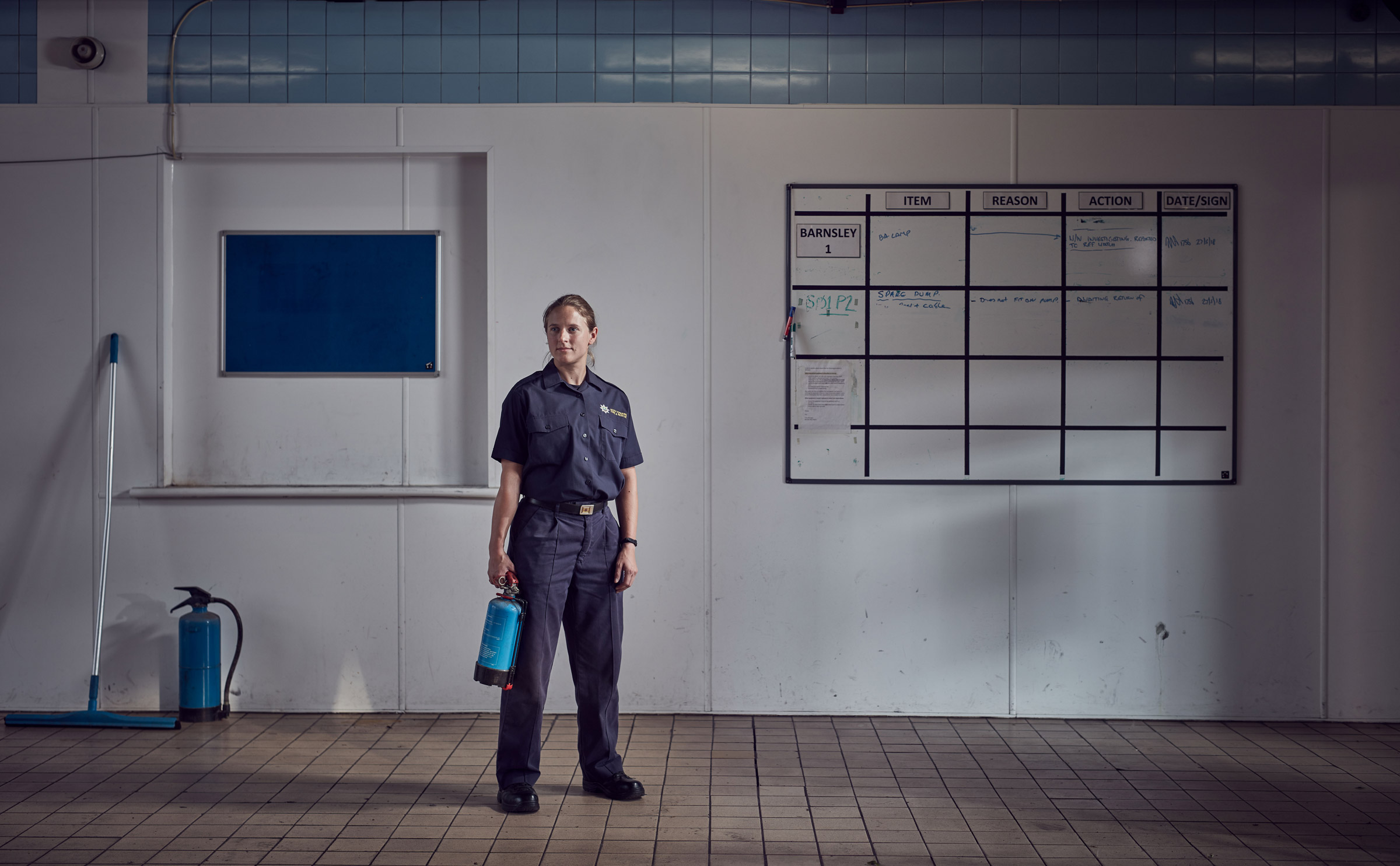 Female firefighter standing in traditional firestation folding extinguisher
