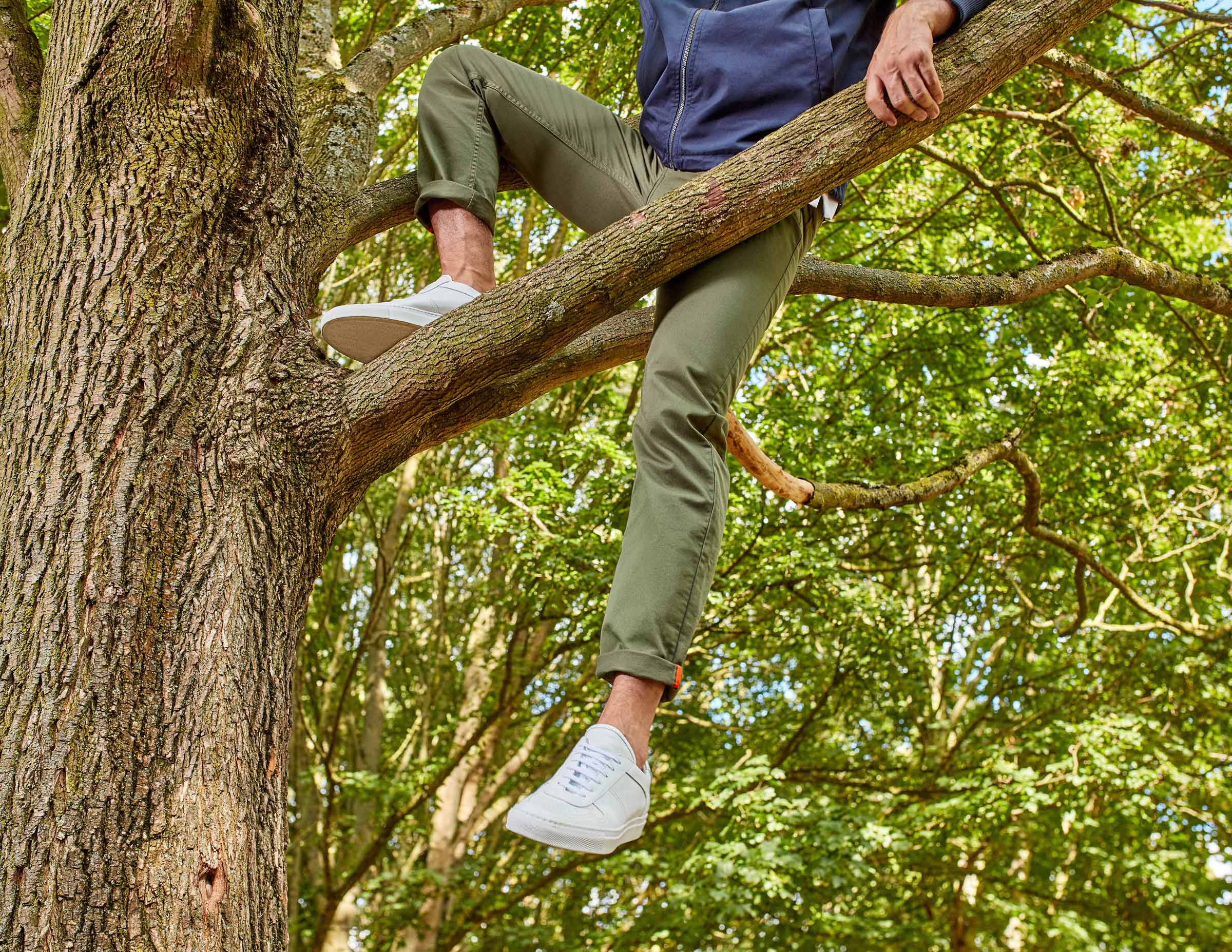 menswear model climbing tree in chinos